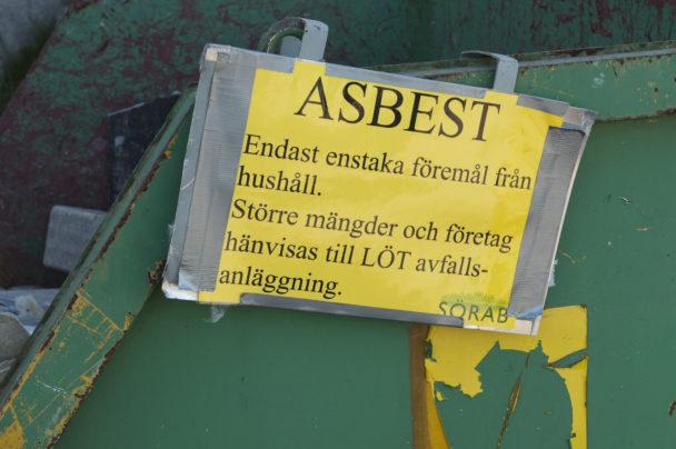 """En grön container med en skylt där det står: """"Asbest. Enstaka föremål från hushåll. Större mängder och företag hänvisas till LÖT avfalls-anläggning. Sörab."""""""