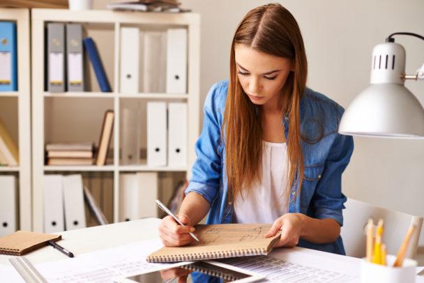 En ung person sitter vid ett skrivbord och skriver med en penna