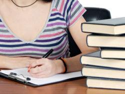 Överkroppen på en ung person som sitter och skriver invid en trave böcker.