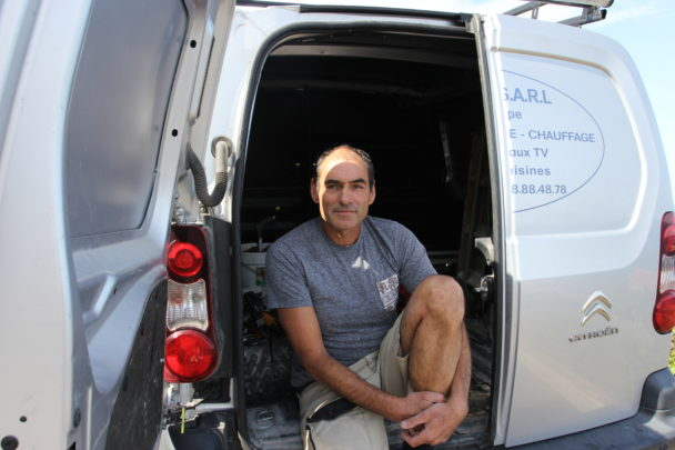 Philippe Requena sitter i den öppna bakdörren på en firmabil.
