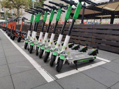En lång rad parkerade elsparkcyklar i stadsmiljö.