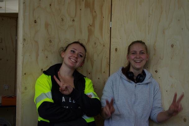 Två glada personer står framför en plywood-vägg. En med armarna i kors och en gör peace-tecknet.