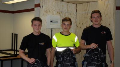 Tre personer står framför en plywood-vägg med varsin ryggsäck i händerna.