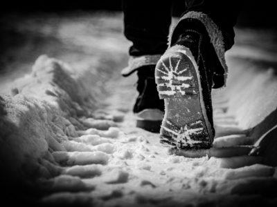 Närbild på ett par fötter klädda i kängor som går i ett traktorspår i snön.
