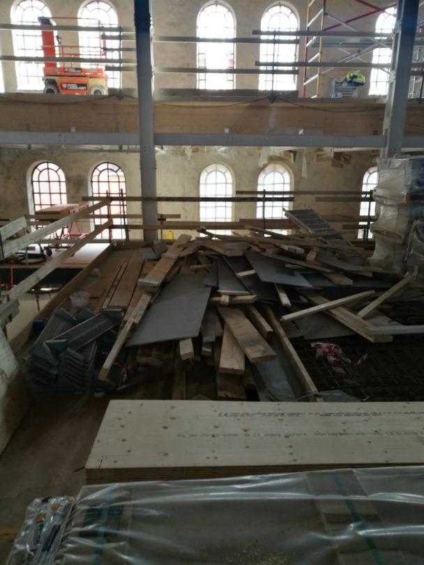 Övervåningen på en arbetsplats. Det ligger brädor på golvet och ett lågt räcke skärmar av mot golvets slut.