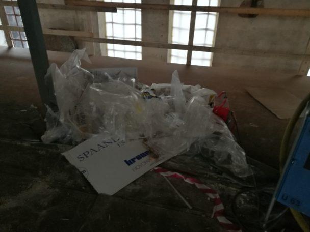 Övervåningen på en arbetsplats. Det ligger bråte på golvet och ett lågt räcke skärmar av mot golvets slut.