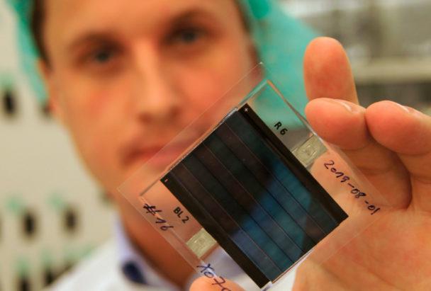 Thomas Österberg håller upp en genomskinlig kvadrat med mörkare celler i mitten.