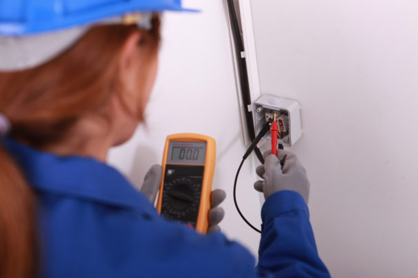 En elektriker i blå kläder och hjälm mäter spänning i ett eluttag.