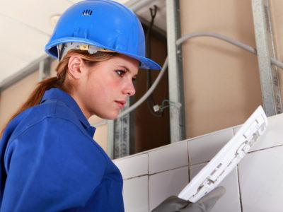 En elektriker i blå kläder och hjälm tottar på ett papper på en arbetsplats.