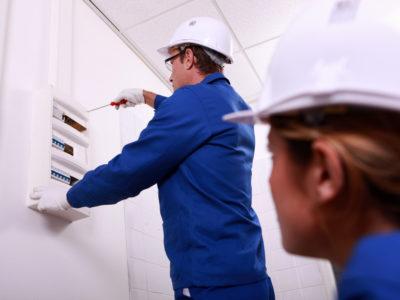En elektriker skruvar i en vägg medan en annan tittar på.