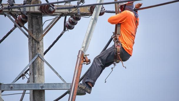 En elektriker uppe i en elstolpe.