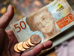 En hand som håller i en svensk 50-lapp och mynt.