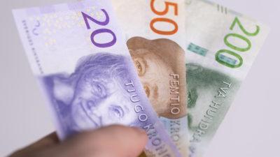 En hand som håller i svenska sedlar