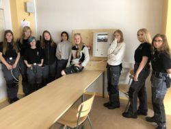 En grupp elever står och sitter i ett klassrum.