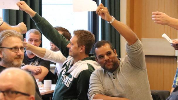 Mötesdeltagare som håller upp röstlappar i luften.