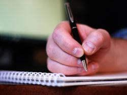 En hand som håller i en penna över ett skrivblock