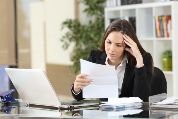 En person sitter vid ett skrivbord med en laptop, och läser bekymrat från ett papper.