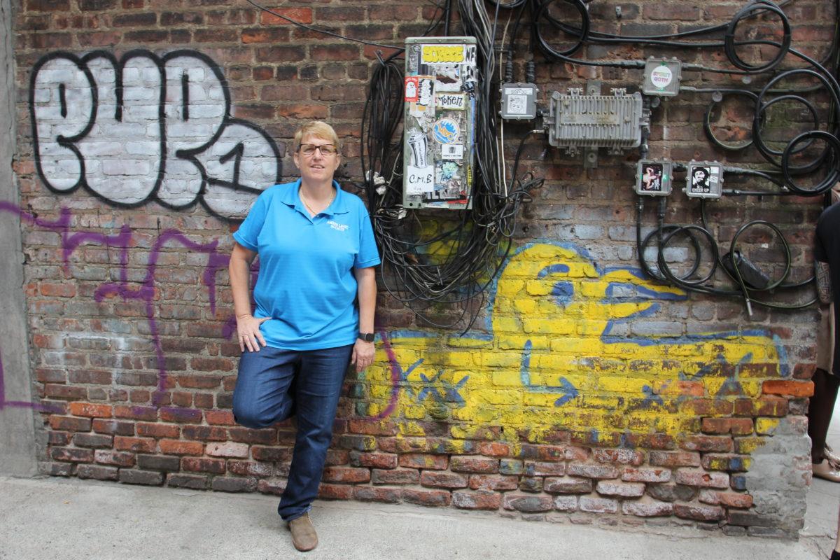 Erin står lutad mot en tegelvägg ful av graffiti, klädd i blå t-shirt.