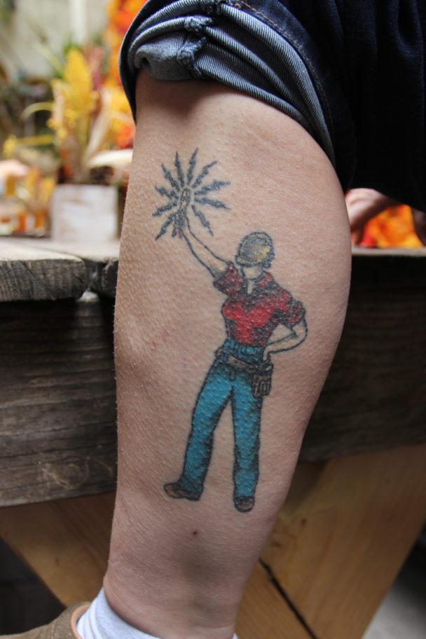 Tatueringen på Erins vad. En kvinnlig elektriker i röd t-shirt och gul skyddshjälem håller upp en el-sprakande tång.