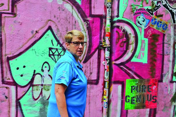 Erin i halvfigur, stående framför en vägg med graffiti.