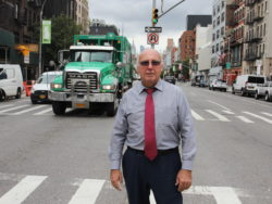 Chris Erikson står på ett övergångsställe med en stadsvy i bakgrunden, bland annat fronten på en stor grön lastbil.