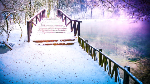 En liten träbro över en frusen vintersjö med träd i bakgrunden.