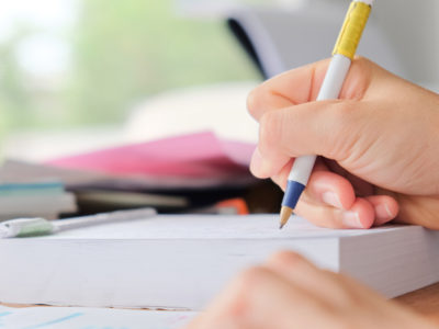 En hand som håller i en penna och skriver i ett block.