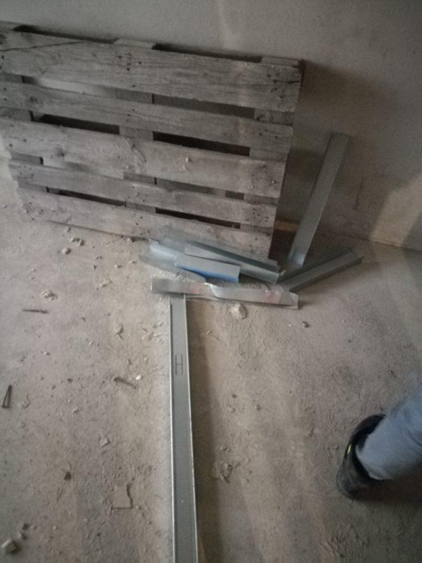 Ett skräpigt golv med en lastpall lutad mot en vägg.