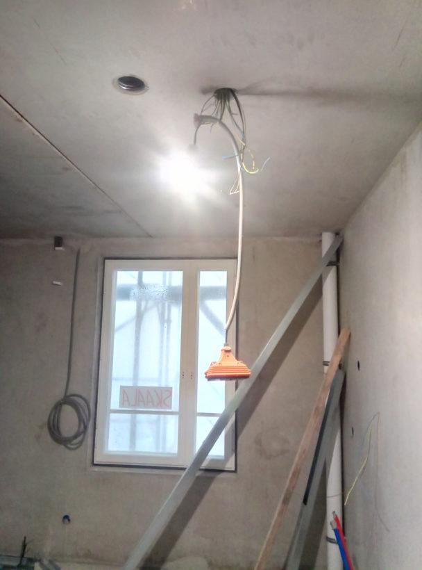EN lampa som hänger från ett tak i ett kalt rum.