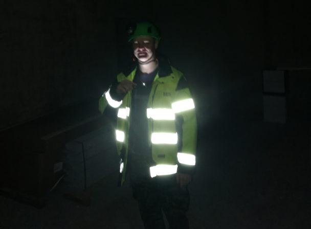 David Wikström står i mörkret. Reflexerna på jackan blänker starkt.