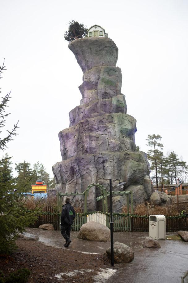 Ett högt, vindlande berg med en stuga på toppen.