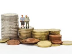 Leksaksfigurer av ett äldre par som står på en trave mynt, bland flera sådana travar.