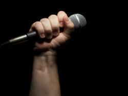 En mikrofon i en knuten hand mot en svart bakgrund.