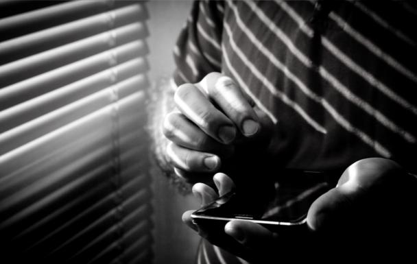 En person står vid ett fönster med sin mobiltelefon