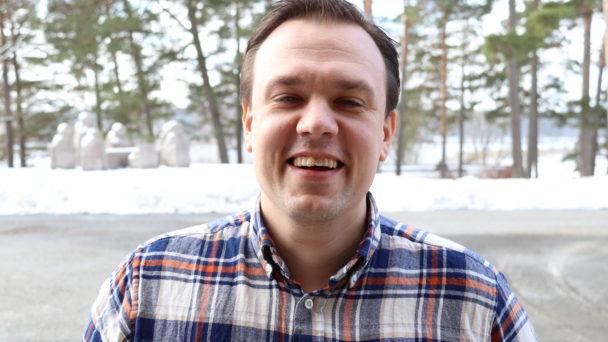 Porträttbild av Per-Ola Nilsson framför en samling träd.