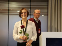 Louise Olsson leende med en ros i händerna.