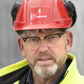Porträttfoto på Johan Lindholm i röd bygghjälm