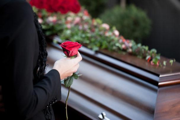 En träkista med blommor på. I förgrunden en person i svarta kläder som håller i en röd ros.