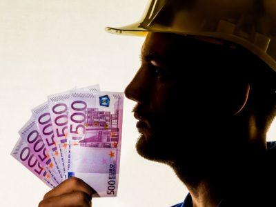 Profil av en person i gul bygghjälm som håller upp en but sedlar framför ansiktet.
