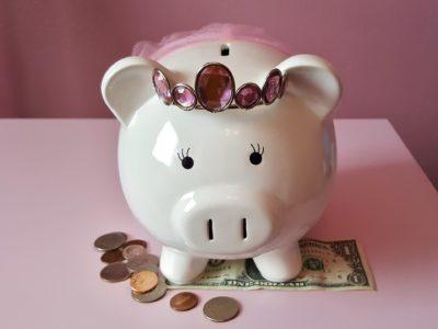 En spargris med krona på huvudet och pengar vid fötterna