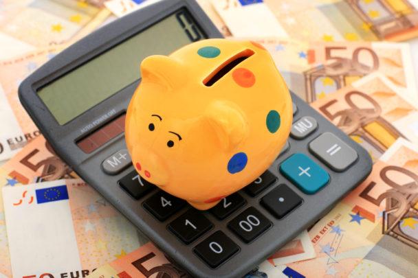 En spargris på en miniräknare och sedlar
