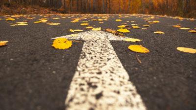 En vit pil målad på en asfaltsväg