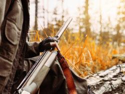 En person sitter utomhus med ett gevär i händerna