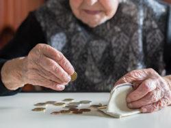 En äldre person räknar mynt på ett bord