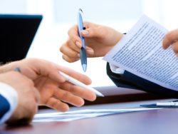 Två par händer som håller i pennor och papper i ett möte