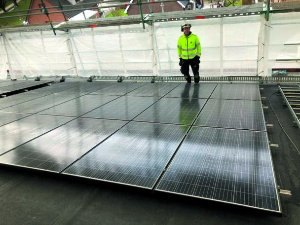 Jakob Bertilsson står invid solcellerna