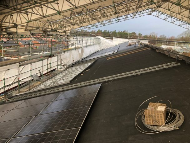 Ett stort utrymme under tak, med solceller och optimerare