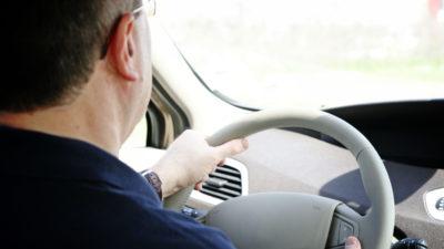 Bild bakifrån på en person som kör bil