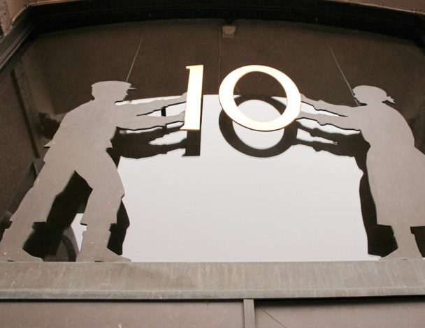 Siffran 10 ovanför A-kassans lokaler på Banhusgatan. Siffran hålls uppe av två silhuett-skulpturer i metall.