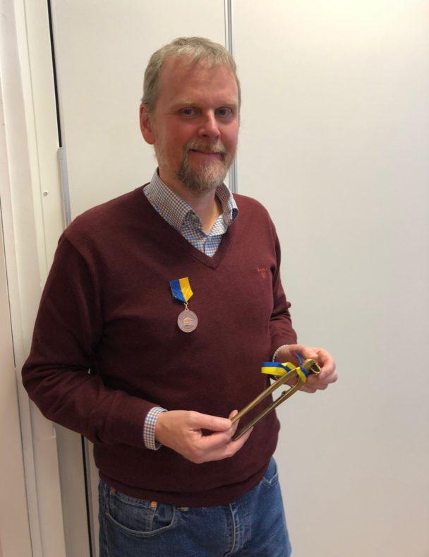 Urban Pettersson med en medalj i händerna.
